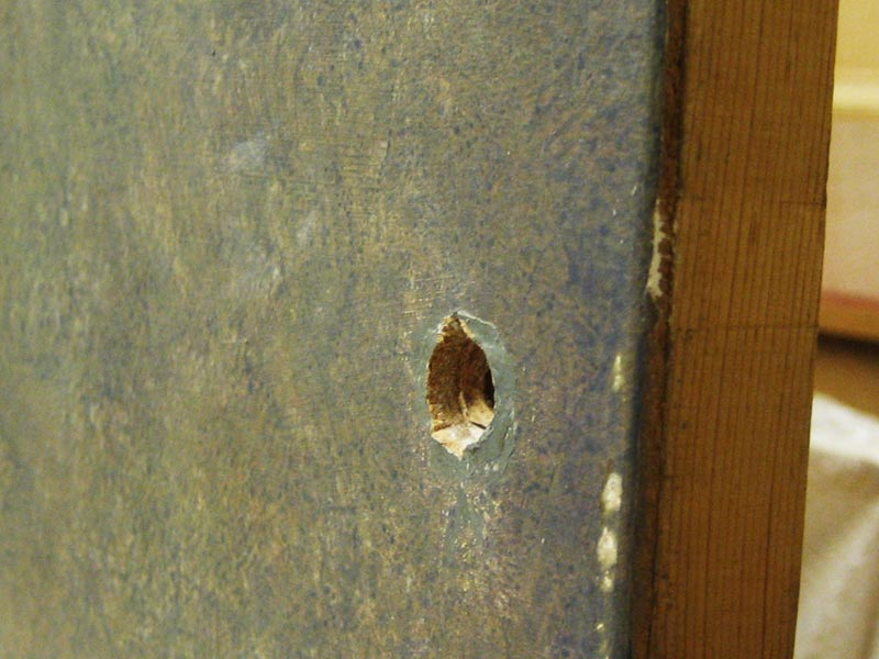 Hole-drilled-through-painting